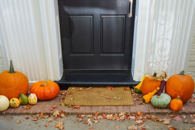 Pumpkins on front steps of home during Halloween/Thanksgiving s
