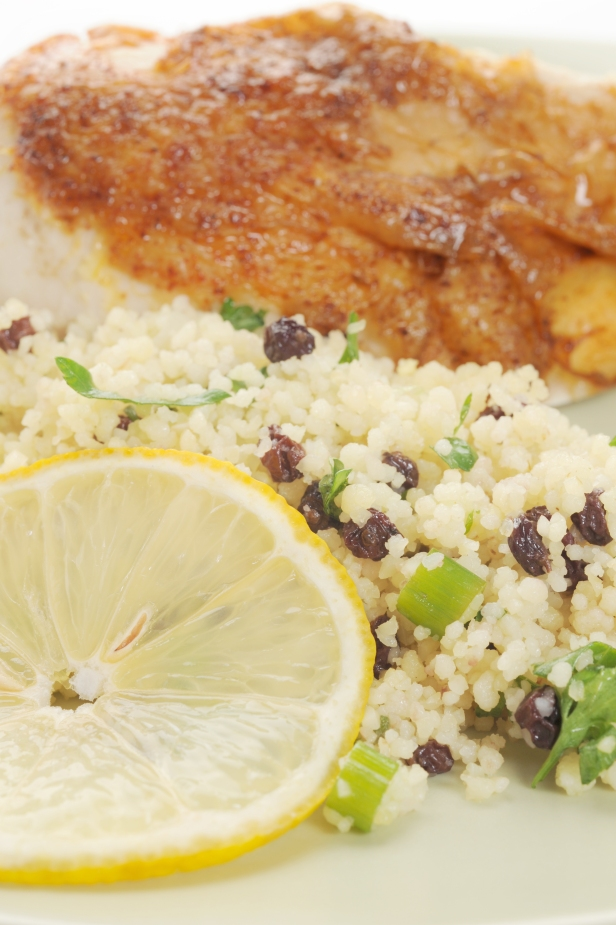 A plate with chicken, couscous and a lemon wedge.