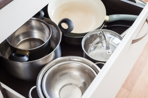 Open drawer of cabinet with steel pots and pans and bowl. Kitchen utensils background